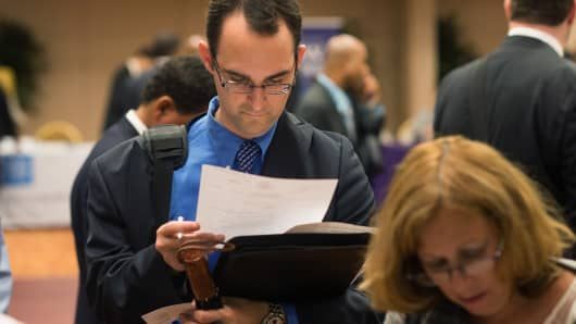 A job seeker reviews his paperwork and resume during a job fair in New York.