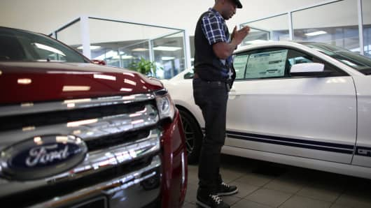 Shopper looks at a Mustang at a Ford dealership in Miami