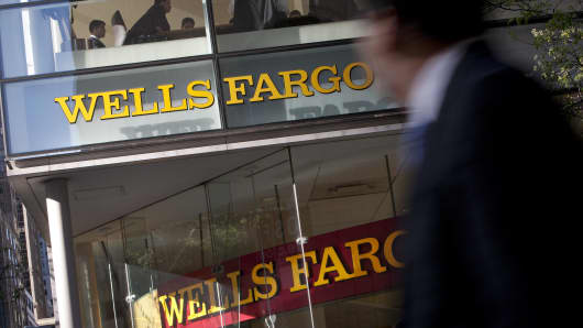Pedestrians walk past a Wells Fargo & Co. bank branch in New York.