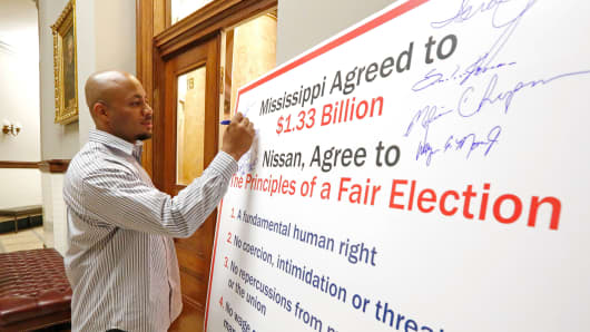 Morris Mock Jr. signs a oversized petition calling for Nissan to allow union recruitment without company opposition, May 17, 2013.