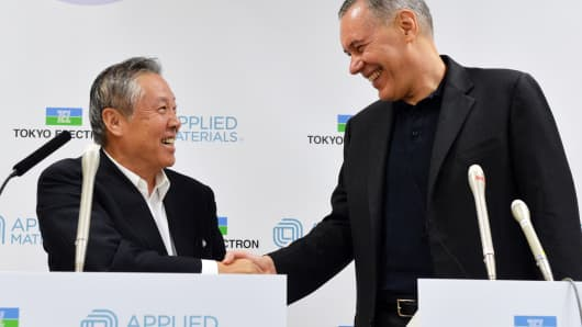 Japan's Tokyo Electron chairman Tetsuro Higashi (L) shakes hands with US semiconductor giant Applied Materials CEO Gary Dickerson (R) after they agreed to merge, at a press conference in Tokyo on September 24, 2013.
