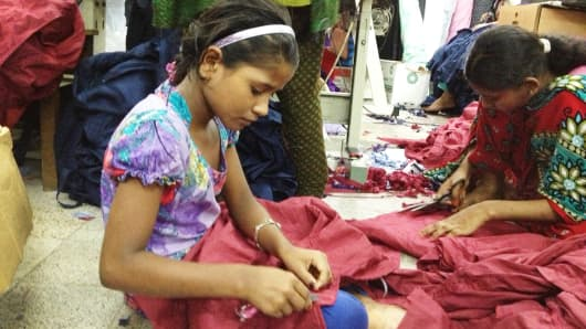 Meem, 9 years old, works inside a garment factory in Dhaka, in Bangladesh. September 23, 2013.
