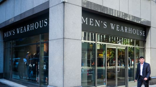 A pedestrian walks by a Men's Wearhouse store in New York.