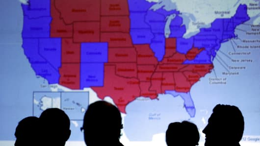Silhouettes of people's heads are seen in front of an 2012 electoral U.S. Map.