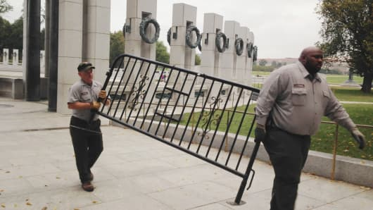 National Park Service personnel remove the barricades from the World war II Memorial In Washington, as the US government reopens October 18, 2013.