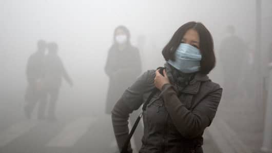 Pedestrians wearing masks walk along a road as heavy fog engulfs the city on October 21, 2013 in Harbin, China.