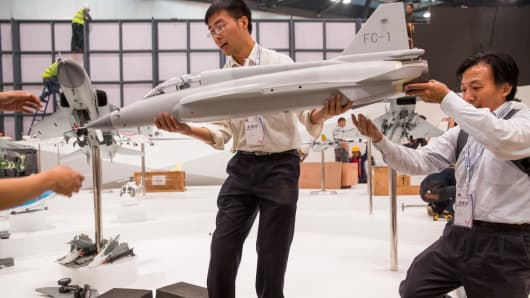 Aviation Industry Corporation of China employees hold a model of the JF-17 fighter jet at an aviation expo in Beijing, Sept. 28, 2013.