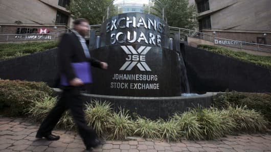 A businessman passes a sign at the entrance to the Johannesburg stock exchange in Johannesburg, South Africa.