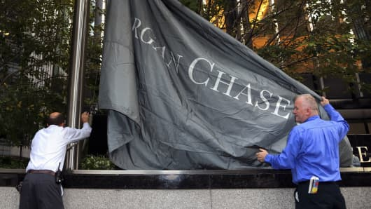 Workmen raise the JP Morgan Chase Inc. flag outside company headquarters in New York.