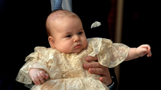 Prince William, Duke of Cambridge arrives, holding his son Prince George, at Chapel Royal in St James's Palace, ahead of the christening of the three month-old Prince George of Cambridge by the Archbishop of Canterbury.