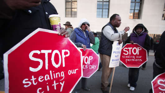 People, mostly union and retired city workers, protest in front of the U.S. Courthouse where Detroit's bankruptcy eligibility trial began this morning October 23, 2013 in Detroit.