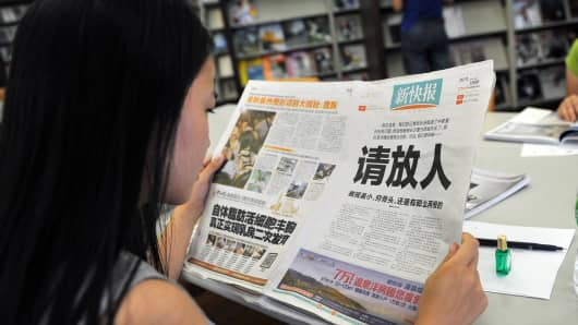 A woman reads the New Express newspaper that on October 23, 2013 carried a full-page editorial with headline 'Please release our man.'