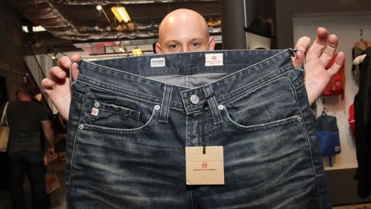 An AG Jeans worker holds up a pair of AG jeans at the GQ & Nordstrom pop-up shop at Nordstrom's Treasure & Bond in New York.