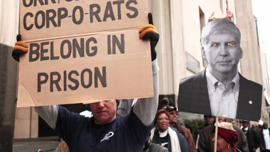 Protestors rally in front of the U.S. Courthouse in Detroit where Detroit's bankruptcy eligibility trial is taking place October 28, 2013 in Detroit, Michigan. Michigan's Governor Rick Snyder is expected to testify today at the trial.