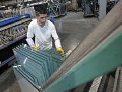 A worker reaches for glass to assemble a double-pane window frame at Crystal Windows & Doors IL Manufacturer in Chicago.