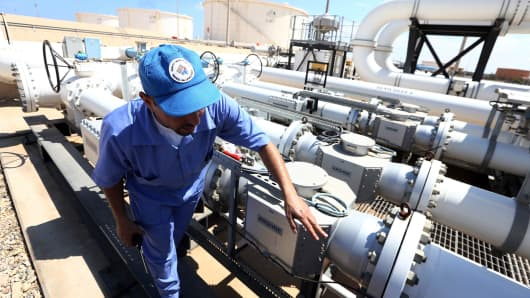 A Libyan oil worker from the Libyan National oil and gas company checks an oil pipelines at the Zawiya oil installation in Zawiya, Libya.