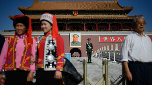 Tourists pose before a paramilitary policeman (centre R) and a portrait of Mao Zedong (back) at Tiananmen Gate and the Forbidden City in Beijing on October 29, 2013.