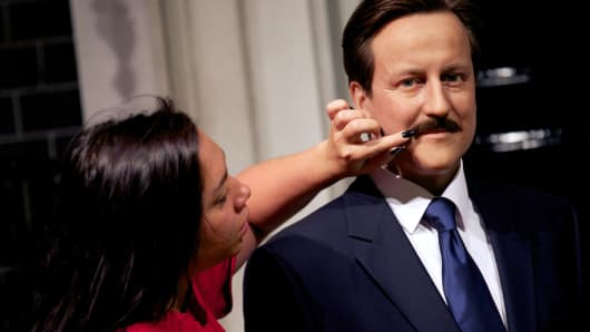 A technician applies a mustache to the wax figure of David Cameron at Madame Tussauds Museum in London