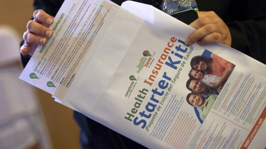 An attendee looks over brochures about affordable health care as she waits in line during the WeConnect Health Enrollment Information & Wellness Event in Oakland, California.