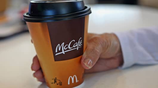 A customer holds a McCafe cup inside a McDonald's Corp. restaurant in Oak Brook, Illinois.