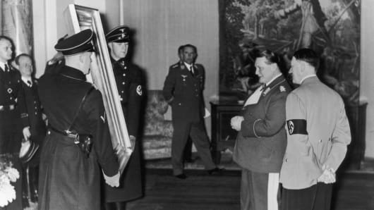 Hermann Goering and Adolf Hitler admire a painting.