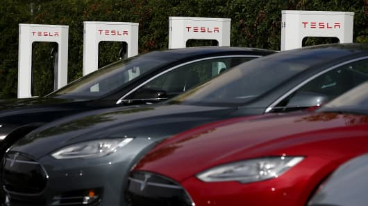 Tesla Model S sedans are seen parked in front of a row of new Tesla Superchargers outside of the Tesla Factory in Fremont, California.