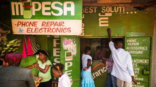 Residents transfer money using the M-Pesa banking service at a store in Nairobi, Kenya, on Sunday, April 14, 2013.