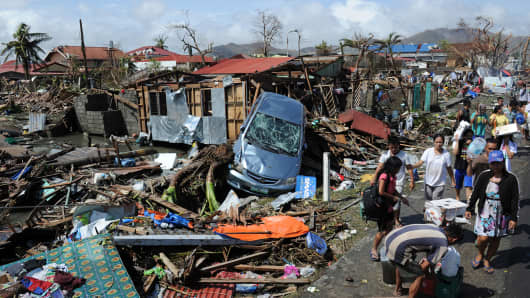 Residents walk past debris and destroyed houses along a road in Tacloban City, Leyte province, central Philippines on November 10, 2013, three days after devastating Super Typhoon Haiyan hit the city on November 8.