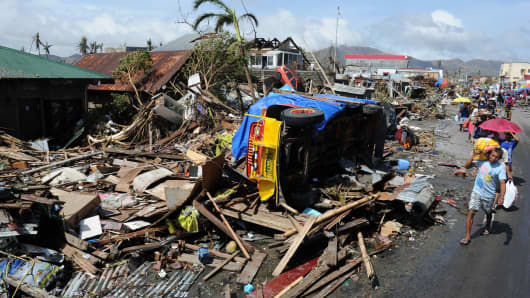 Residents walk past debris and an overturned jeepney littered along a road in Tacloban City, Leyte province, central Philippines.