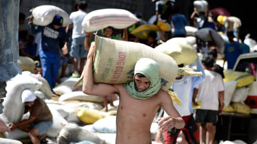 Residents loot water damaged sacks of rice from a rice warehouse in Tacloban in the eastern Philippine island of Leyte on November 11, 2013.