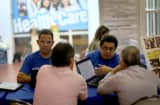 Insurance agents with Sunshine Life and Health Advisors help people with information about policies that are available to them under the Affordable Care Act at a kiosk setup at the Mall of Americas on No