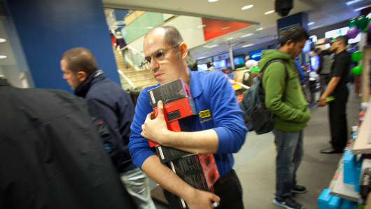 A Best Buy employee in New York restocks items on Black Friday last year.
