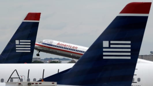 An American Airlines jet takes off behind US Airways jets at Ronald Reagan Washington National Airport in Arlington, Virginia.