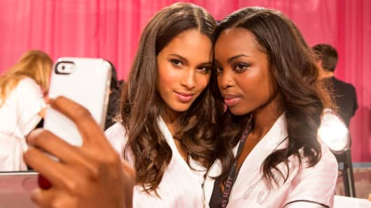 "Models backstage at the Victoria's Secret Fashion Show taking a ""selfie""."