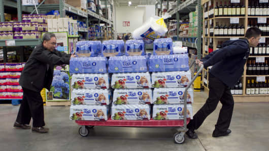 Customers move a cart full of water through a BJ's Wholesale Club Inc. store in Falls Church, Virginia.