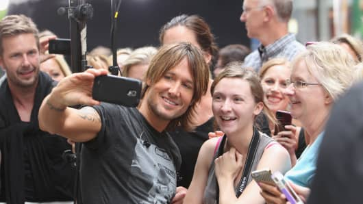 Musician Keith Urban takes a selfie photo with a fan, September 2013.