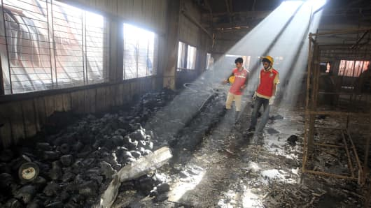 Bangladeshi rescue workers look on at the scene following a blaze that engulfed a garment factory in Sripur on October 9, 2013.