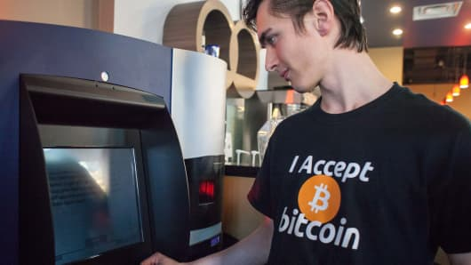 "Gabriel Scheare uses the world's first bitcoin ATM on October 29, 2013, at Waves Coffee House in Vancouver, British Columbia. Scheare said he ""just felt like being part of history.&qu"