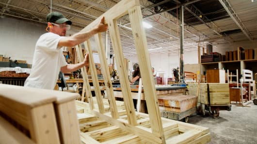 An employee stacks bunk bed framing onto a cart in the working area at the Bunk & Loft Factory in Columbus, Ohio.