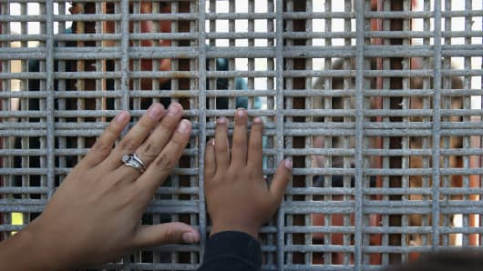 Family members reunite through bars and mesh of the U.S.-Mexico border fence in San Diego.