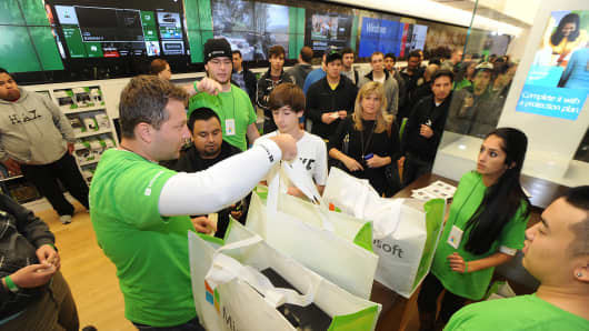 Customers receive the new Xbox One during the midnight launch event at the Microsoft retail store at Tysons Corner Center in McLean, Virginia.