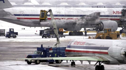 File photo: An American Airlines jet awaits departure as another is de-iced at O'Hare International Airport in Chicago.