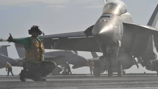 A U.S. Navy Aviation Boatswain's Mate signals to launch an F/A-18E Super Hornet aircraft from the flight deck of the aircraft carrier USS George Washington (CVN 73) in the South China Sea