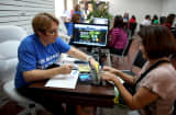 Mercy Cabrera (L), an insurance agent with Sunshine Life and Health Advisors, helps Amparo Gonzalez purchase an insurance policy under the Affordable Care Act at the store setup in the Westland Mall in Hialeah, Florida.