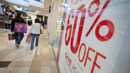 Shoppers walk past a sale sign displayed outside of a Gap store.