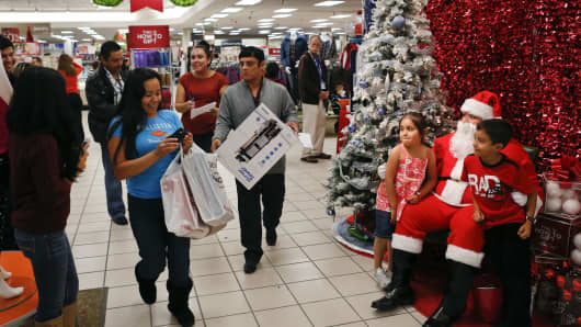 Children pose for pictures with Santa Claus at a Sears store during the Family and Friends evening sale inside the Del Amo shopping mall in Torrance, California.