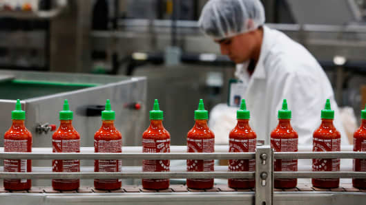 Bottles of Sriracha hot sauce travel down a conveyor belt to be boxed for shipment at the Huy Fong Foods facility in Irwindale, Calif.