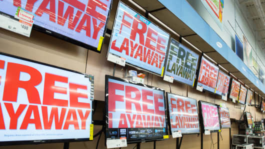 Free Layaway service signs appear on TVs at Walmart in King of Prussia, Pa., Nov. 12, 2013.