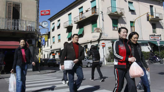 Chinese youths walk along Pistoiese street, one of the main roads of Prato, Italy.