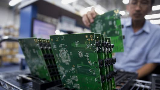 An employee adds a circuit board to a rack in the manufacturing area at the Patton Electronics Co. headquarters in Gaithersburg, Maryland.